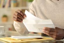 Black Man Hands Putting A Letter Inside An Envelope