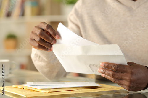 Cuadros en Lienzo Black man hands putting a letter inside an envelope