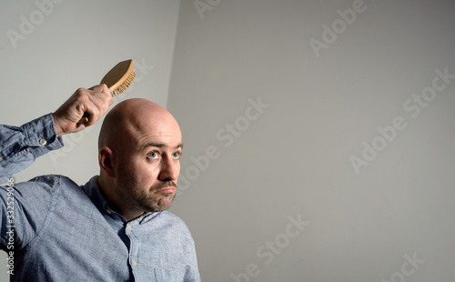 Confused bald man with hair brush Canvas Print
