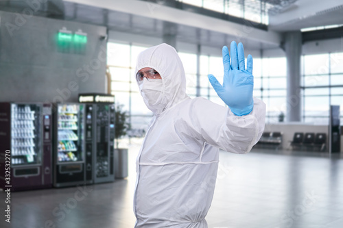 Fotografie, Obraz epidemiologist in a protective suit shows a prohibition gesture against the wait