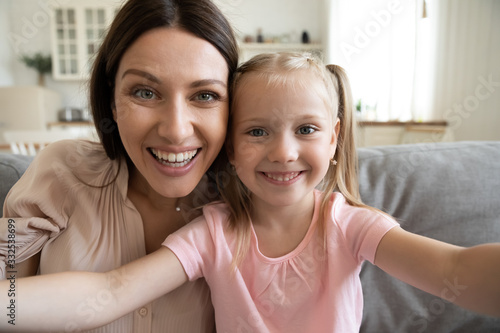 Fototapeta Smiling young mother and small preschooler daughter look at camera making selfie at home together, happy funny mom and little girl child have fun laugh take photo posing for self-portrait picture obraz
