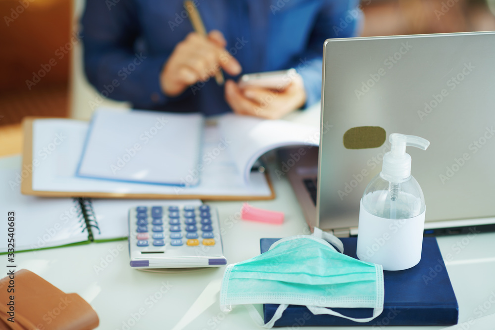 Fototapeta medical mask and hand disinfectant and woman working