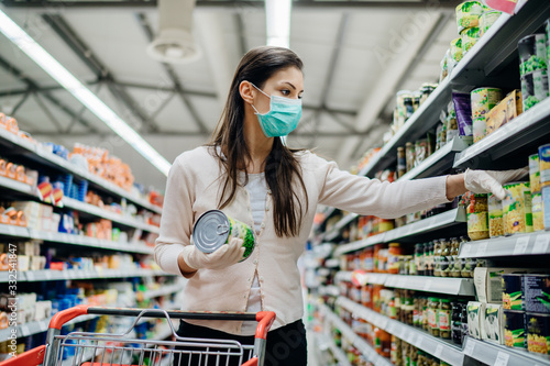 Obraz Woman preparing for pathogen virus pandemic spread quarantine.Choosing nonperishable food essentials.Budget buying at a supply store.Pandemic quarantine preparation.Emergency to buy list - fototapety do salonu