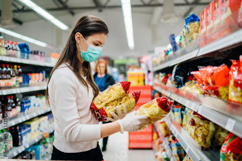 Fototapeta Buyer wearing a protective mask.Shopping during the pandemic quarantine.Nonperishable smart purchased household pantry groceries preparation.Woman buying few pasta packages.Budget pastas and noodles. obraz