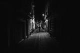 Fototapeta Uliczki - Woman walking alone in the street late at night.Narrow dark alley,unsafe female silhouette.Empty streets.Woman pedestrian alone.Police hour.Assault situation,violence against women concept.