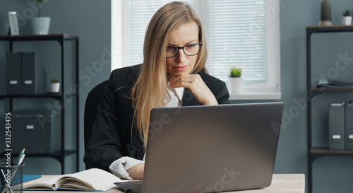 Vászonkép Focused mature business lady in formal suit and specs working on laptop sitting