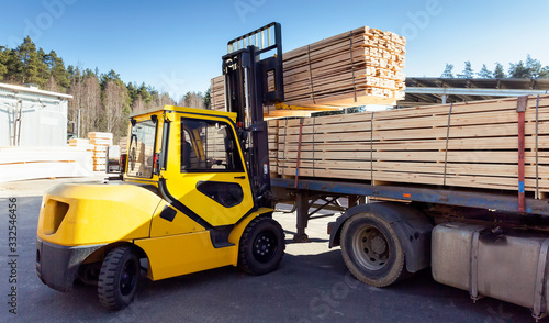Obraz The machine loads the boards, lumber from the finished goods warehouse onto the truck - fototapety do salonu
