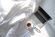 canvas print picture - Top view of laptop and hot coffee in bed with soft sunlight in the morning