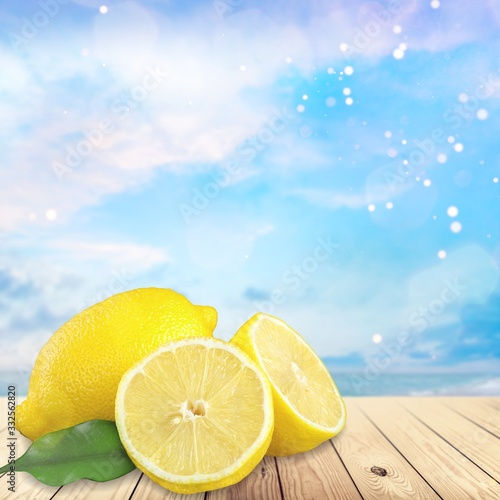 Whole and cut fresh yellow lemon on wooden desk