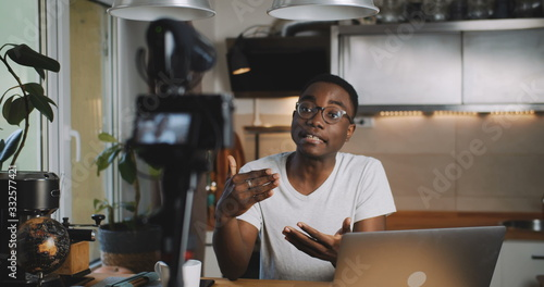 фотография Happy young smart black blogger man filming new vlog video with professional camera in kitchen at home slow motion