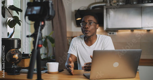 Photo Happy young smart black blogger man filming new vlog video with professional camera in kitchen at home slow motion