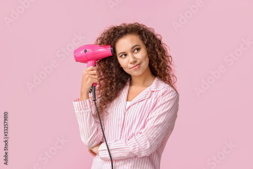 Tela Beautiful young African-American woman with blow dryer on color background