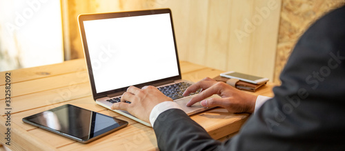 Businessman wearing black formal suit using laptop computer working from home office. Male manager using software for online conference with his company team. Blank screen for advertising on desktop
