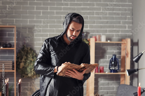Male alchemist with spell book in laboratory Wallpaper Mural
