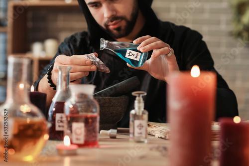 Fototapeta Male alchemist making elixir in laboratory
