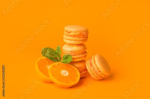 Fototapeta Tasty macarons with orange fruit on color background obraz