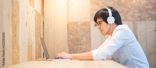 Fototapeta Young Asian man wearing headphones listening to music while working with laptop computer. Male office worker doing online conference with his business company team. Work from home concept obraz