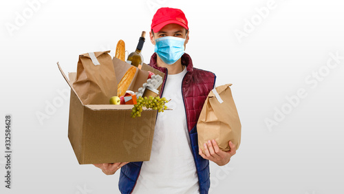Fototapeta Delivery man holding paper bag with food on white background, food delivery man in protective mask obraz