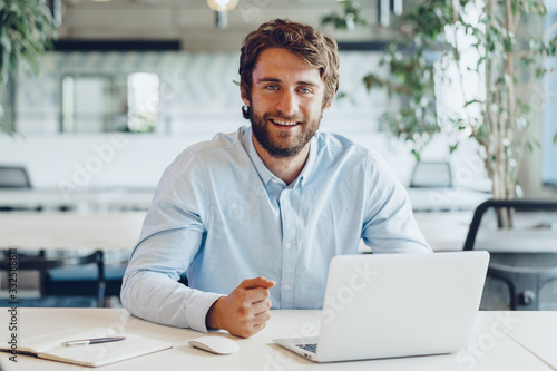 Foto Businessman in shirt working on his laptop in an office