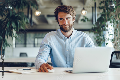 Obraz Businessman in shirt working on his laptop in an office. Open space office - fototapety do salonu