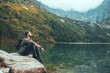 man sitting on the rock in front of lake in mountains enjoying the view