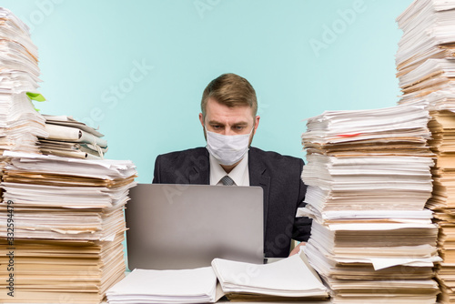 Photo A male accountant or company manager works in an office in a pandemic in view of the accumulated paper work