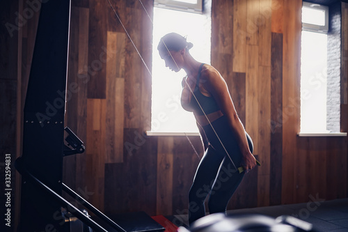 Fototapeta Determined young woman working out on row machine in fitness studio. obraz