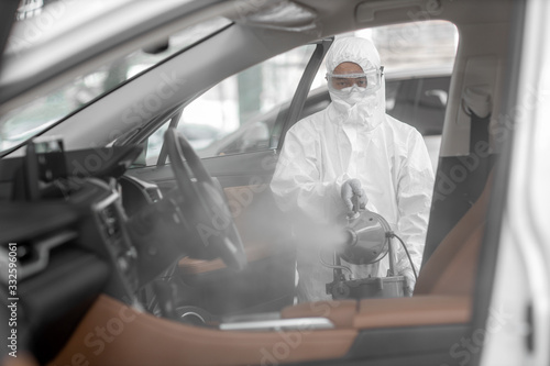 Obraz Disinfectant worker character in protective mask and suit sprays bacterial or virus in a car. - fototapety do salonu