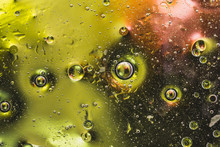 Multicolored Abstraction. A Few Drops Of Oil On The Water. Backlit Background. Green And Black