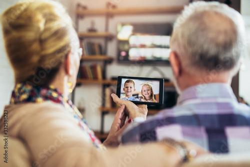 Obraz Senior couple making video call on digital tablet with their grandchildren.Quarantine. Health concept. - fototapety do salonu