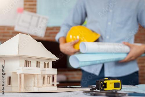 Fototapeta Close up architectural model, engineer man is holding blueprint and safety helmet obraz