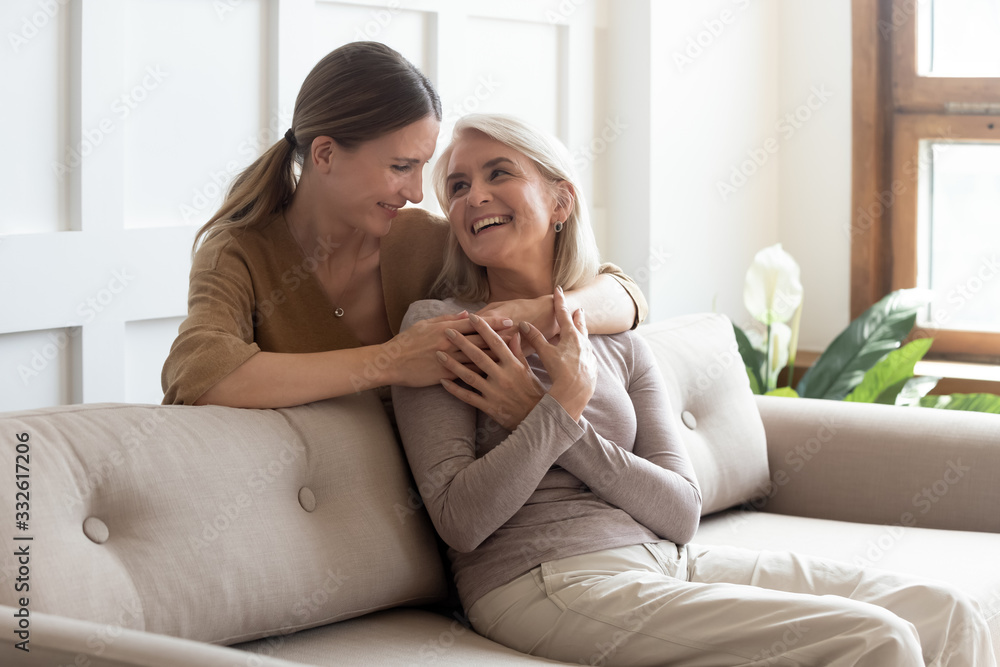 Fototapeta Loving adult daughter hugging older mother, standing behind couch at home, family enjoying tender moment together, young woman and mature mum or grandmother looking at each other, two generations
