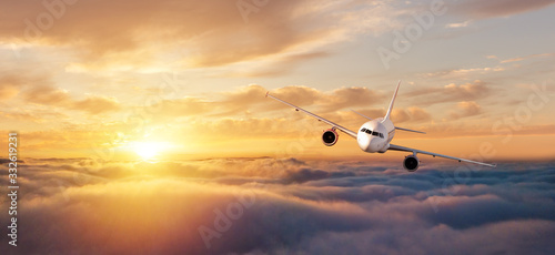 Photo Commercial airplane flying over dramatic sunset