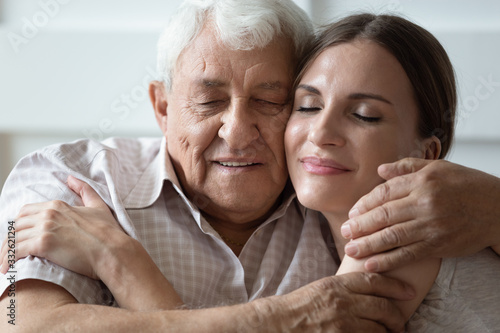 Obraz Happy adult daughter and older father hugging and cuddling with closed eyes close up, expressing love and gratitude, enjoying tender moment, young woman and mature dad or grandfather touching cheeks - fototapety do salonu