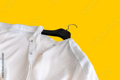Photo White silk blouse on black hanger on yellow background. Top view