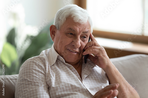 Smiling older man talking on cellphone close up, happy grandfather chatting with Fototapete