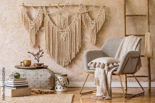 Fototapeta Stylish oriental living room with design armchair, beautiful macrame, big pouf, decoration, carpet, tray and elegant personal accessories in wabi sabi concept