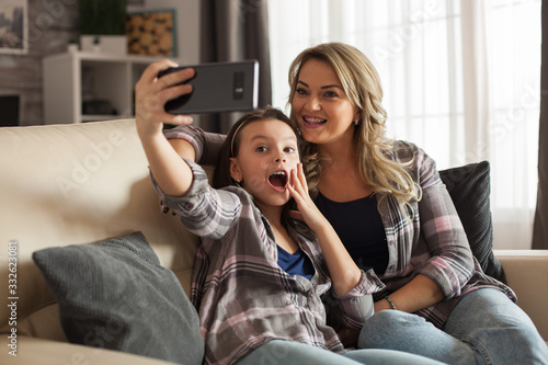 Fototapeta Excited daughter taking a selfie with her mother obraz