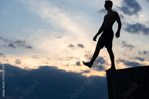 Fototapeta Silhouette of man against background of clouds and sunset