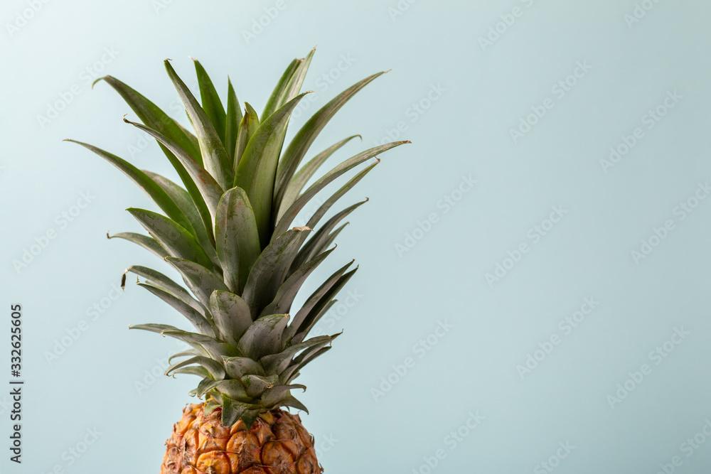 Fototapeta Whole pineapple on pastel blue background. Copy space.