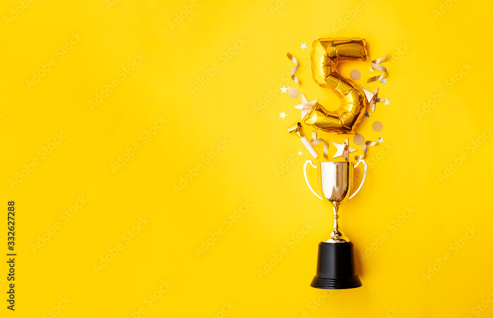 Fototapeta Number 5 gold anniversary celebration balloon exploding from a winning trophy