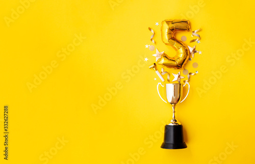 Fototapeta Number 5 gold anniversary celebration balloon exploding from a winning trophy obraz
