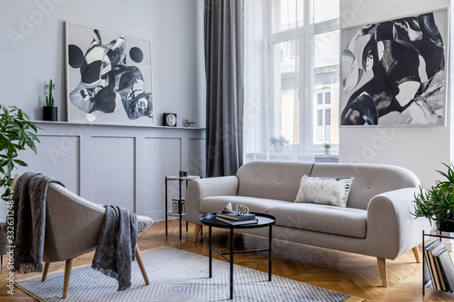 Fototapeta Stylish scandinavian home interior of living room with design gray sofa, armchair, marble stool, black coffee table, modern paintings, decoration, plant and elegant personal accessories in home decor