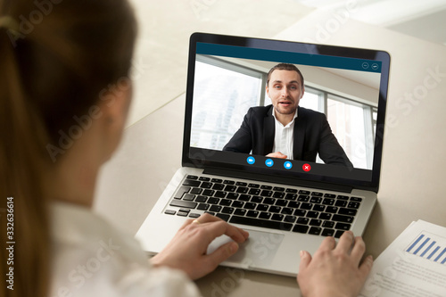 Fototapeta Back view of female employee talk with male businessman on webcam laptop conference, woman worker negotiate with man employer brainstorm on video call from home, online consultation concept obraz na płótnie