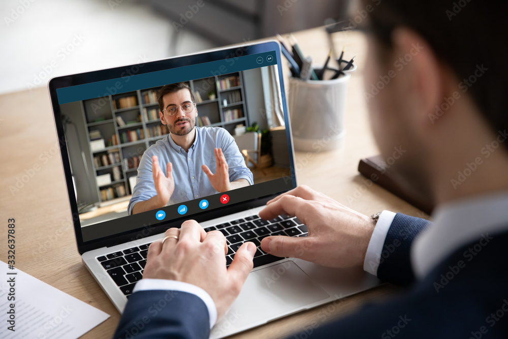 Fototapeta Back view of businessman talk with male business partner using video call on laptop discuss work project online, male client talk with colleague or coworker, speak on webcam conference on computer