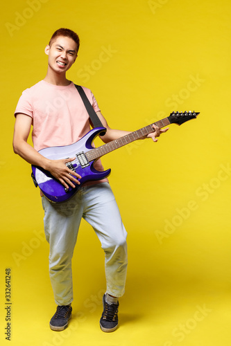 Full length Handsome young musician playing the guitar and singing, isolated on Fototapet