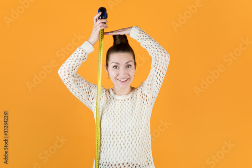 Fototapeta smiling adult girl holds measuring tape next to her and measures her height