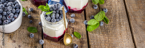 Fototapeta Sweet healthy yogurt with blueberry and blueberry jam in small portioned jars on wooden rustic table, copy space obraz