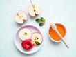 Roter halbierter Apfel auf einem Teller und eine weiße Schüssel mit Honig auf einem hellgrünen Hintergrund, Flat lay, gesunde Ernärhung