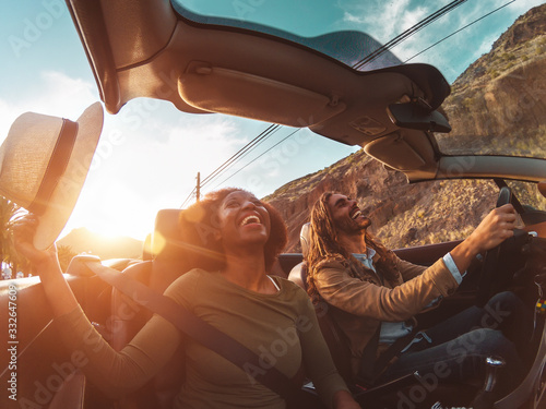 Obraz Happy young couple doing road trip in tropical city - Travel people having fun driving in trendy convertible car discovering new places - Relationship and youth vacation lifestyle concept - fototapety do salonu